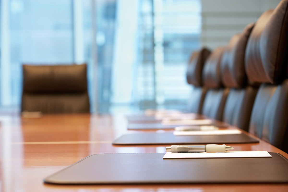 Image shows an empty boardroom table ready for a meeting.