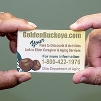 Image is a close-up that shows two people holding a Golden Buckeye Card in their fingertips as if they are passing it from one person to the other.