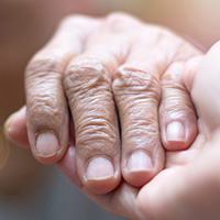 Image is a close-up shot of a young person holding an older person's hand.