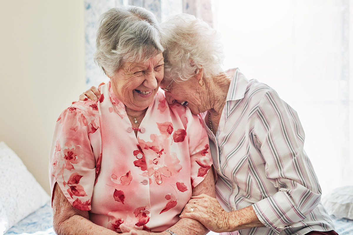 Two older women laugh and embrace as they sit together on a bed.