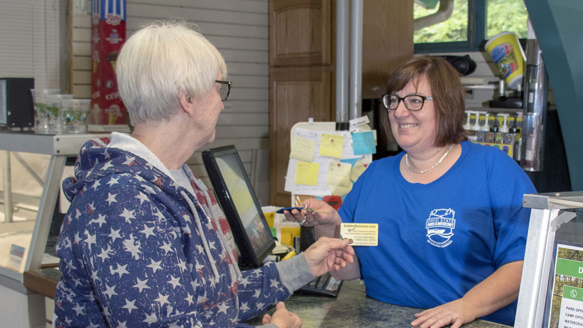 Image shows an older customer handin her Golden Buckeye Card to a cashier at a store.