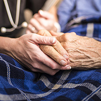 Image is a close-up shot of an older woman and a younger woman holding hands atop a blue checkered blanket. Part of a stethoscope can be seen in the background.