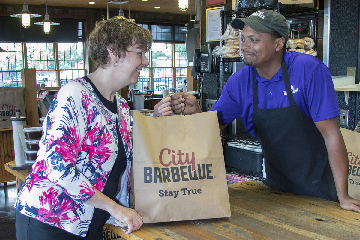 Image shows a customer receiving a bag of carry-out food from a worker at City Barbeque.