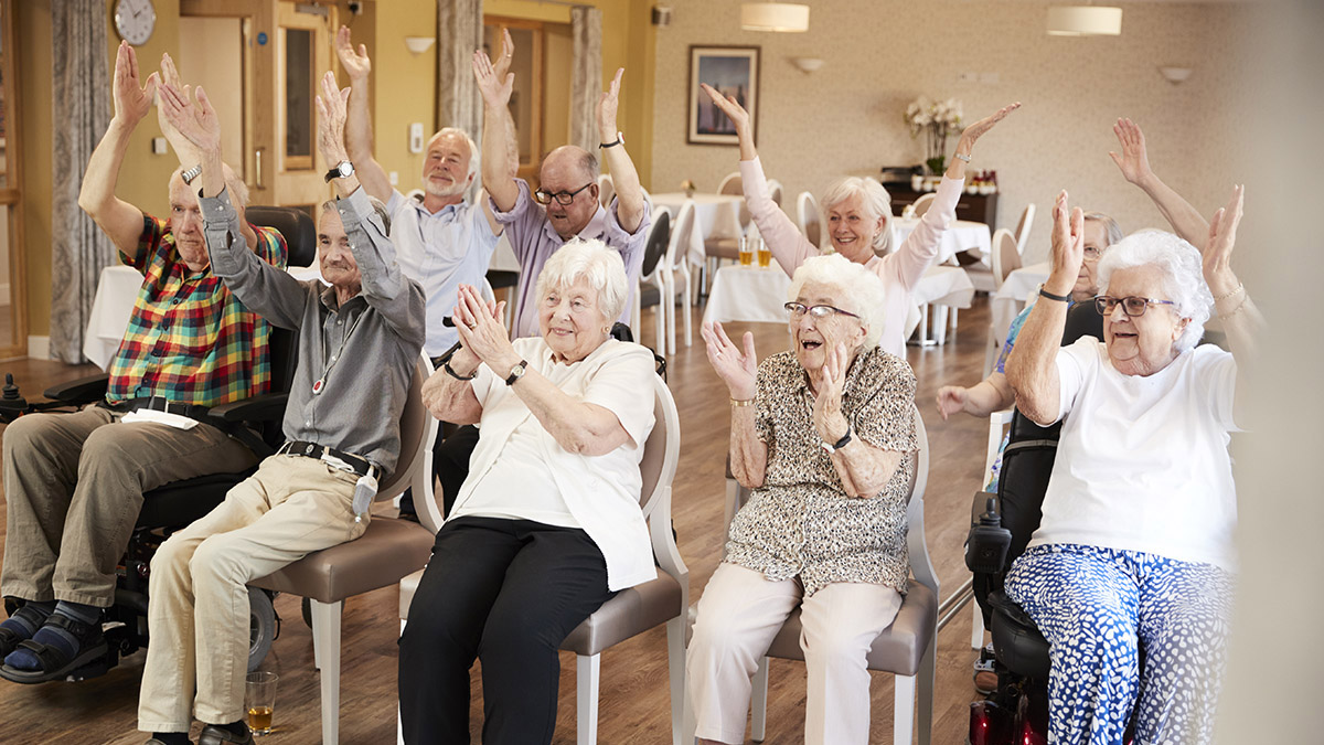 A group of older adults sit in chairs arranged in two rows. They are smiling and lifting their arms above their heads in a group exercise.