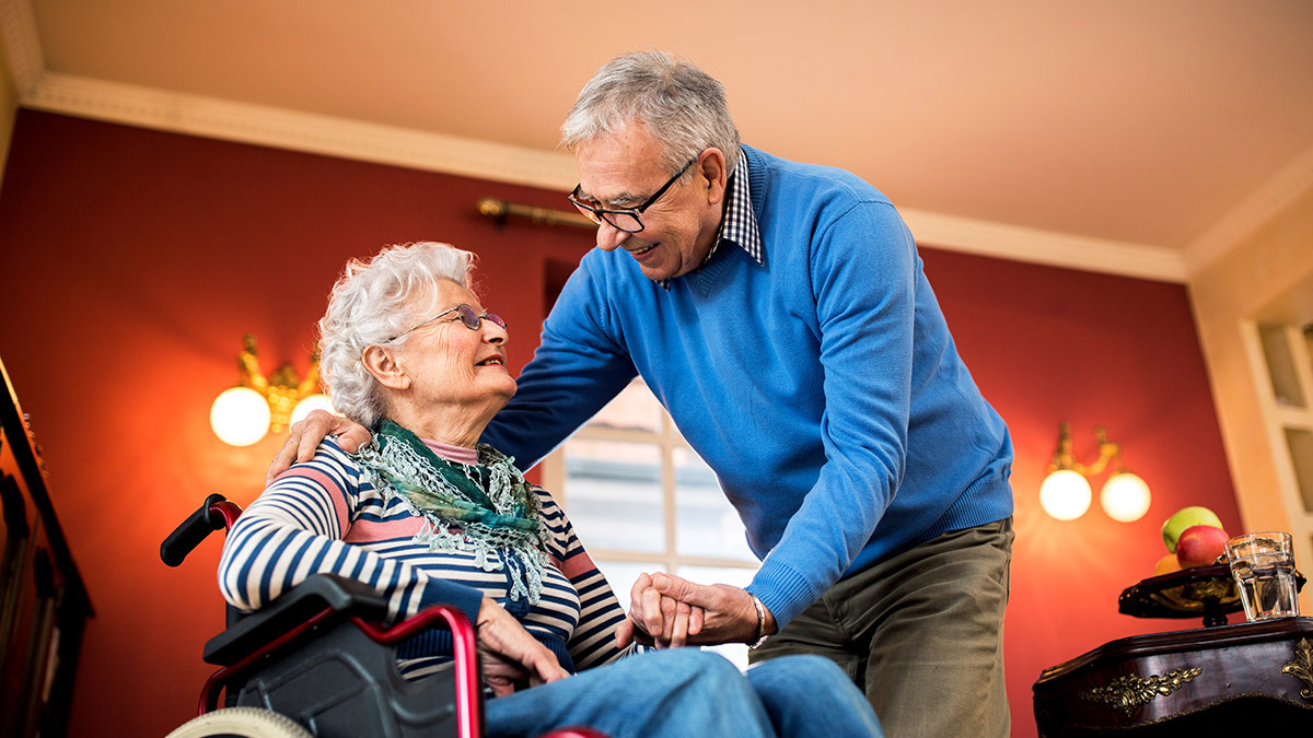 Image shows an older man speaking with an older worman in a wheelchair as he holds her hand.