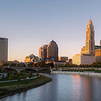Image shows the Columbus, Ohio, skyline at dusk. The Scioto river is in the foreground and several buildings are in the background.