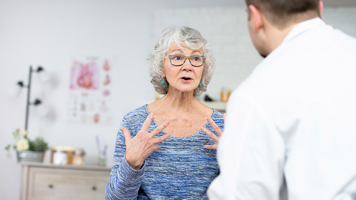 An older woman gestures as she speaks with a doctor in his exam room.
