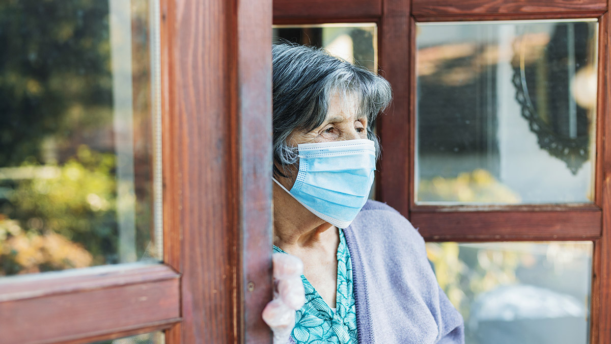 Image shows a nursing home resident wearing protective gloves and mask going outside for a visit.