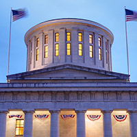 Images shows the Ohio Statehouse rotunda from the outside, lit up at night. Wind is blowing the flags.