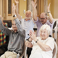 Image shows a group of older adults doing seated exercises together. They are smiling and holding both arms over their heads.